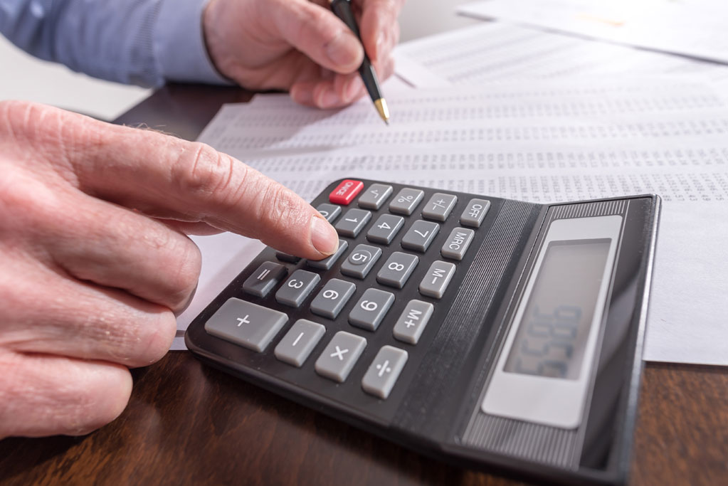 Man doing taxes with calculator, Property Tax Services, Assessment Advisors