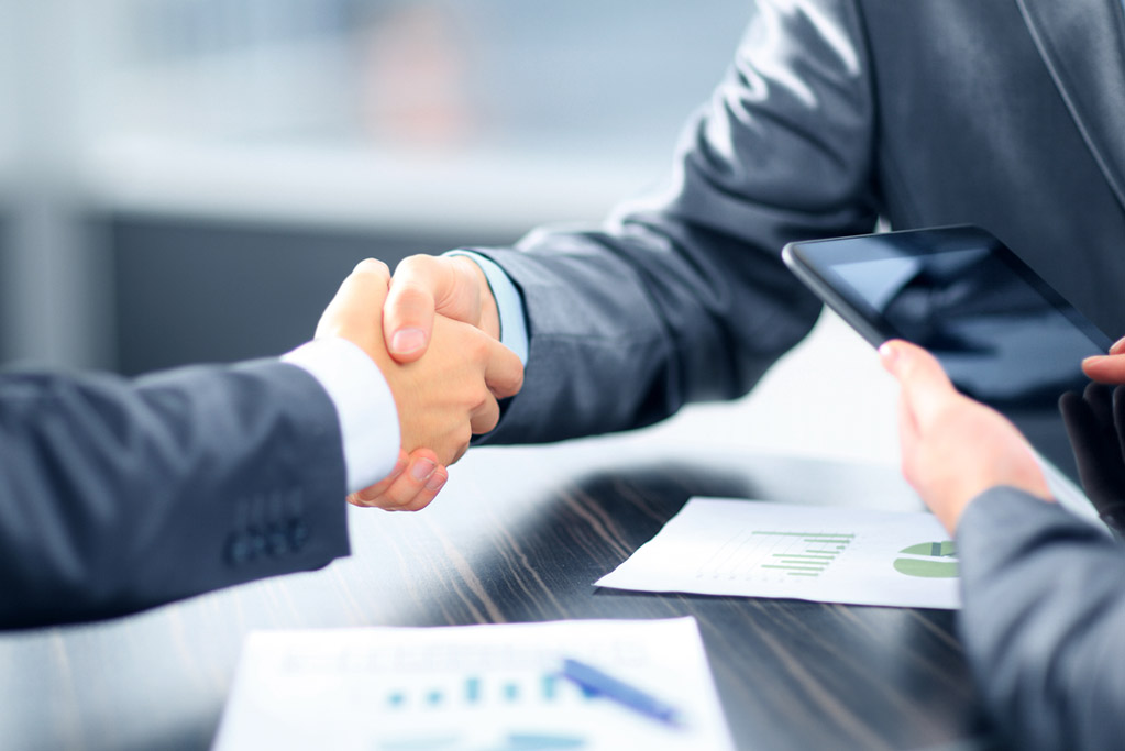 Business people shaking hands in office for business personal property tax services, Assessment Advisors